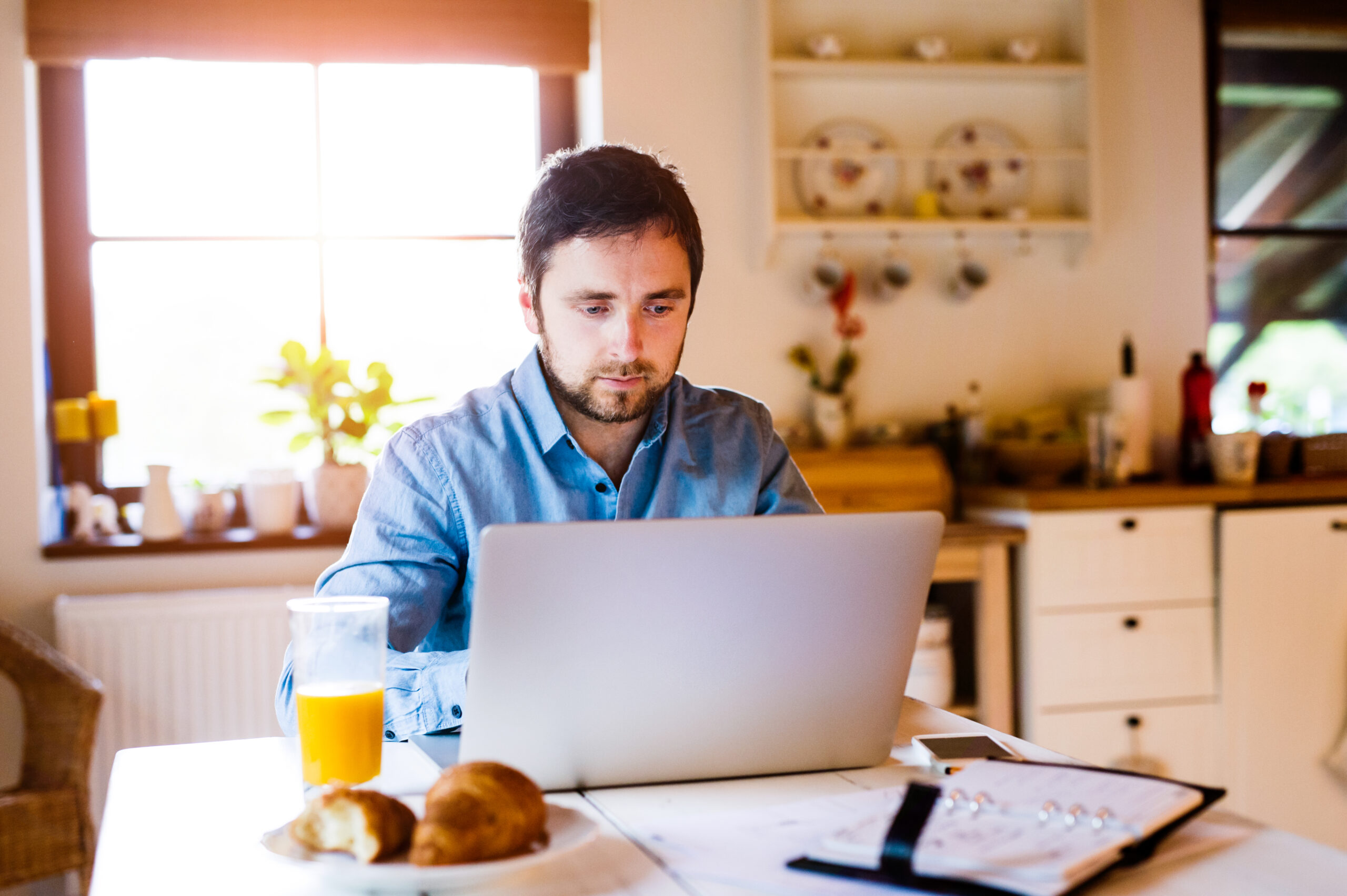 Man sitting at desk working from home with a leased laptop laptop
